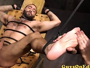 Tattooed stud gets edged by dom duo
