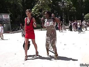 Ebony slave receives lezdom in public